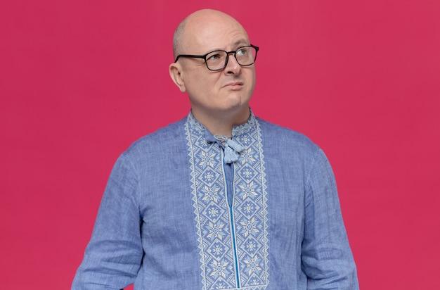 Doordachte volwassen slavische man in blauw shirt met optische bril die omhoog kijkt