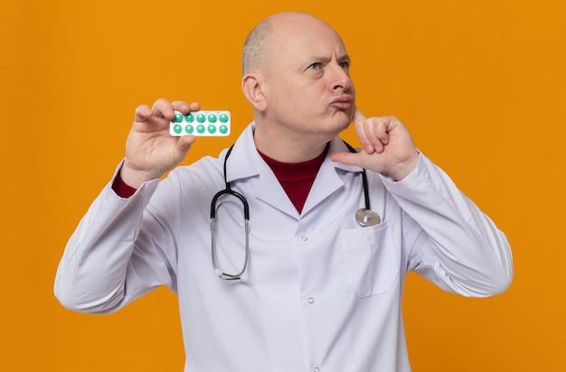 Doordachte volwassen slavische man in doktersuniform met stethoscoop die medicijnblisterverpakking vasthoudt en omhoog kijkt
