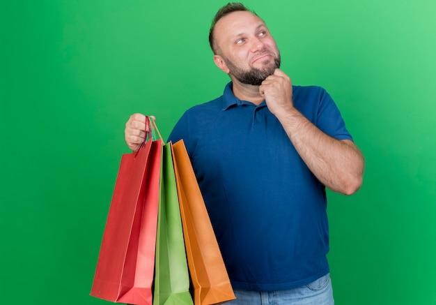 Doordachte volwassen slavische man met boodschappentassen kin aanraken kant geïsoleerd op groene muur te houden