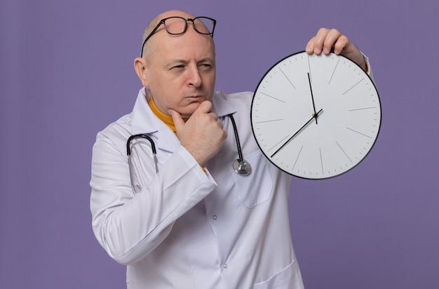 Doordachte volwassen slavische man met bril in doktersuniform met stethoscoop die klok vasthoudt