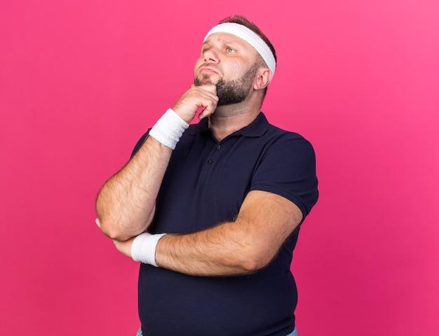 Doordachte volwassen slavische sportieve man met hoofdband en polsbandjes met kin en kijkend naar kant geïsoleerd op roze muur met kopieerruimte