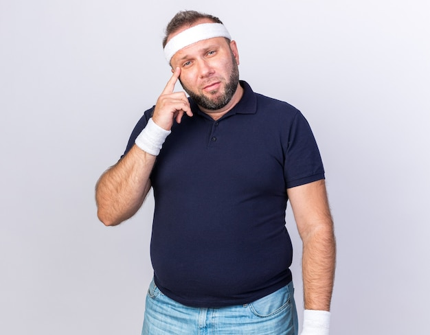 Doordachte volwassen slavische sportieve man met hoofdband en polsbandjes vinger zetten tempel geïsoleerd op een witte muur met kopie ruimte