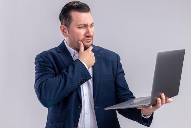 Doordachte volwassen slavische zakenman die laptop vasthoudt en bekijkt die op een witte muur met kopieerruimte wordt geïsoleerd