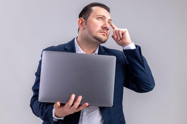 Doordachte volwassen slavische zakenman die laptop vasthoudt en omhoog kijkt