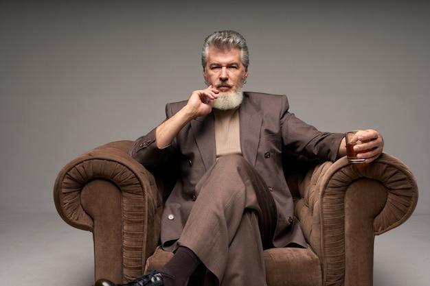 Doordachte volwassen zakenman met baard die een elegant pak draagt en naar de camera kijkt met een glas wijn
