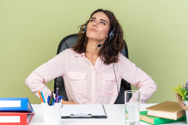 Doordachte, vrij blanke vrouwelijke callcenter-operator op een koptelefoon die aan het bureau zit met kantoorhulpmiddelen die omhoog kijken