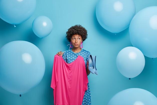 Doordachte vrouw feestganger kiest feestelijke kleding voor speciale gelegenheid, houdt roze jurk op hangers en schoenen met hoge hakken, heeft peinzende uitdrukking, geïsoleerd op blauwe muur, ballonnen rond