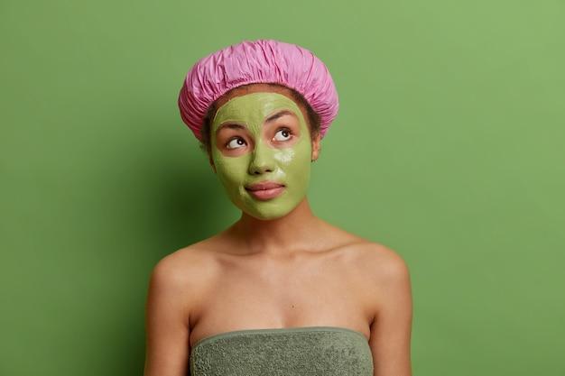 Doordachte vrouw geconcentreerd boven draagt groen gezichtsmasker op gezicht voor verjonging draagt badmuts handdoek rond lichaam denkt na over hoe mooi ziet geniet van huidverzorgingsbehandelingen