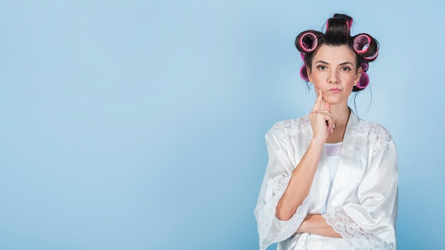 Doordachte vrouw in krulspelden en badjas