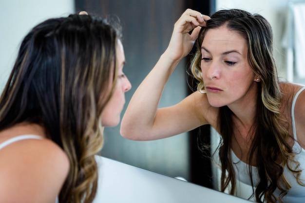 Doordachte vrouw inspecteert haar uiterlijk in de badkamerspiegel