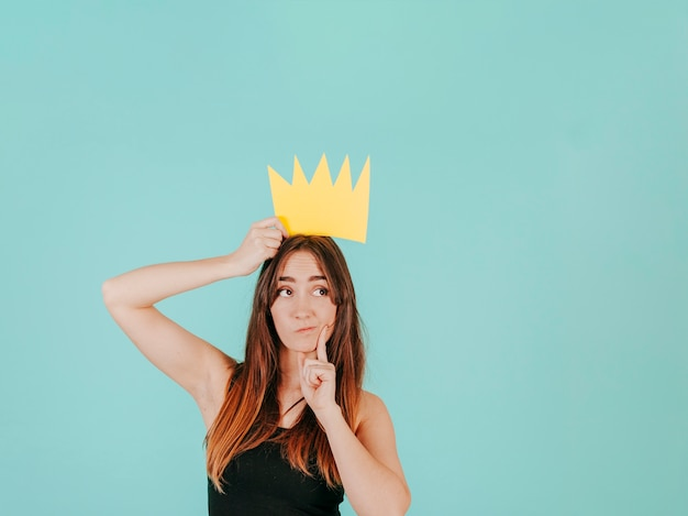 Doordachte vrouw met papieren kroon