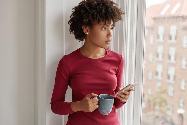 Doordachte vrouw poseren met mobiele telefoon in haar huis