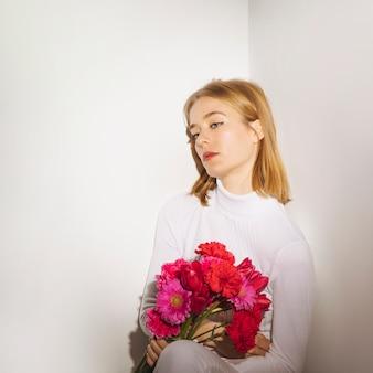 Doordachte vrouw zitten met heldere bloemen