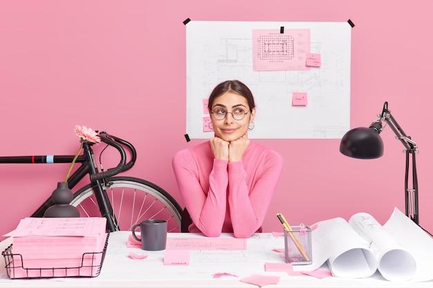 Doordachte vrouwelijke architect plant nieuw project maakt schetsen en blauwdrukken houdt van creatieve oplossingen in gedachten heeft productieve baan zit op desktop werkt vanuit huis plant interieur van toekomstig gebouw