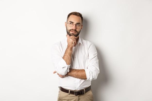 Doordachte zakenman met een bril die een plan maakt, naar de linkerbovenhoek kijkt en denkt, staande tegen een witte achtergrond