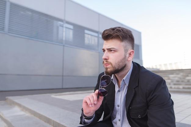 Doordachte zakenman zit op straat op de achtergrond van de moderne architectuur.