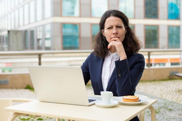 Doordachte zakenvrouw met laptop op zoek