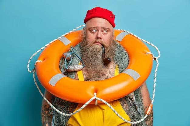 Doordachte zeeman draagt een opgeblazen ringboei om de nek, klaar om mensen op zee te redden, heeft een dikke lange baard, rookt pijp