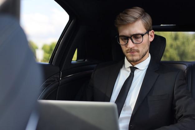 Doordachte zelfverzekerde zakenman die in de luxe auto zit en zijn laptop gebruikt.