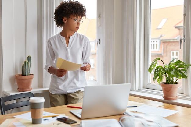 Doordachte zwarte jonge administratief werker bereidt maandelijks verslag voor, staat in de buurt van werkplek met laptopcomputer