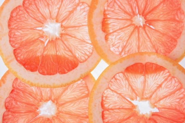 Doorschijnende grapefruitplakken op een witte achtergrond, citrusvruchtenplakken