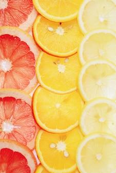 Doorschijnende plakjes citroen, sinaasappel en grapefruit op een witte achtergrond, plakjes citrusvruchten, zomermix