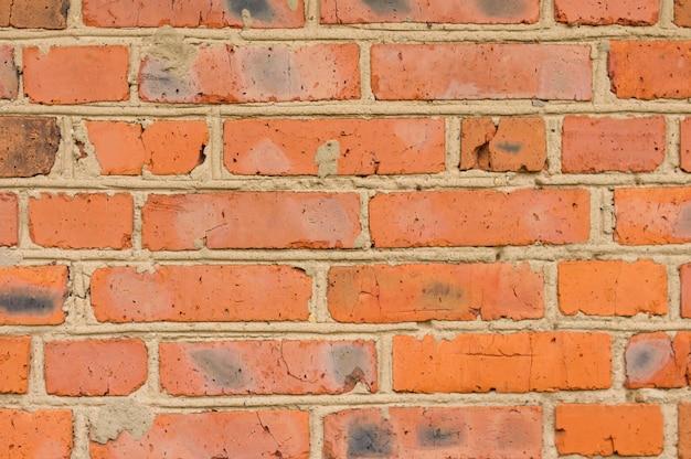 Doorstane rood bevlekte oude bakstenen muurachtergrond.