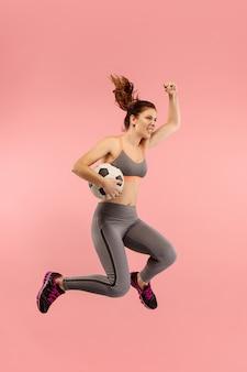 Doorsturen naar de overwinning. de jonge vrouw als voetballer springen en de bal schoppen in de studio op een rode achtergrond. voetbalfan en wereldkampioenschap concept