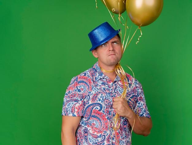 Doortastende jonge partij kerel draagt blauwe hoed bedrijf ballonnen vastgebonden rond nek geïsoleerd op groen met gesloten ogen