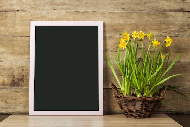 Doorzichtig bord en een vaas met lentebloemen op een houten ondergrond. het concept van het begin van de lente, vakantie. kopieer ruimte.
