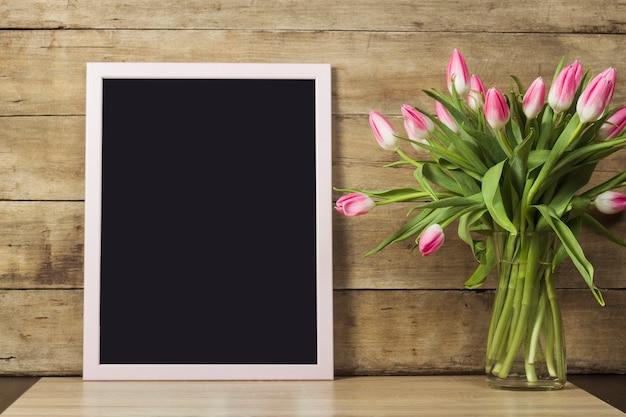 Doorzichtig bord, vaas met tulpen op houten oppervlak. het concept van het begin van de lente, vakantie. kopieer ruimte.