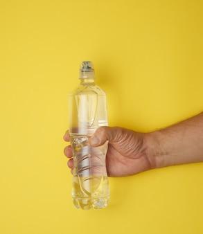 Doorzichtige plastic fles met zoet water in een mannenhand op een geel