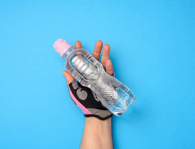 Doorzichtige plastic fles met zoet water in een vrouwelijke hand op een blauwe achtergrond, close-up