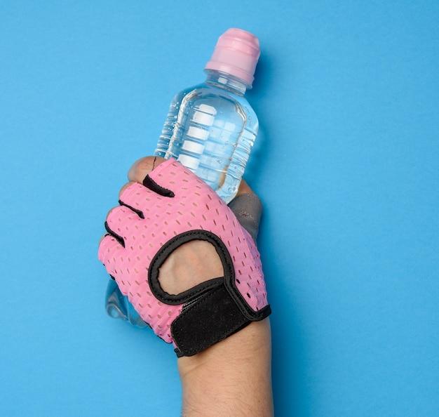 Doorzichtige plastic fles met zoet water in een vrouwelijke hand op een blauwe achtergrond