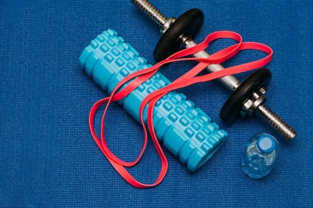 Doorzichtige plastic fles water en plastic halters voor sport en fitness op een blauwe mat