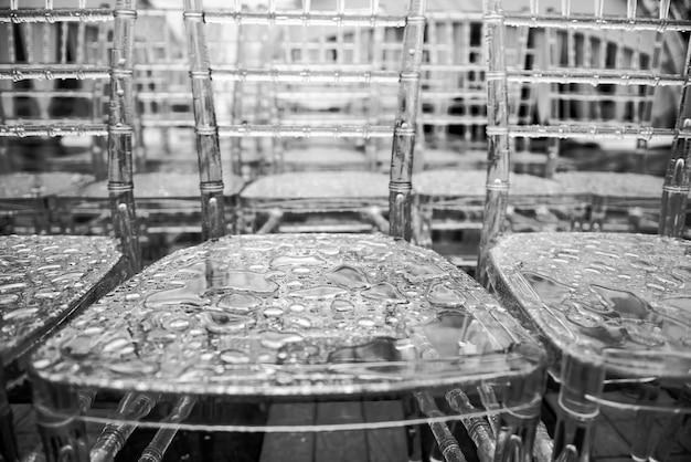 Doorzichtige plastic stoelen met regendruppels op het oppervlak, macro. close-up - waterdalingen op grijze oppervlakte, gebruik voor webontwerp en abstracte textuur als achtergrond.