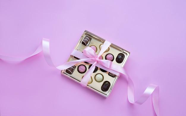 Doos met chocoladepralines met roze strik op roze achtergrond