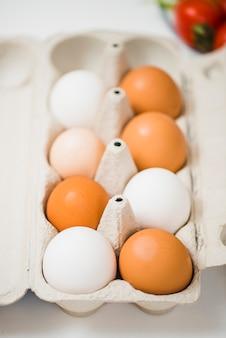 Doos met eieren op tafel in de buurt van tomaten