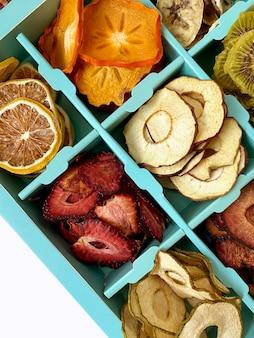 Doos met gedroogde vruchten chips geïsoleerd op wit, bovenaanzicht.