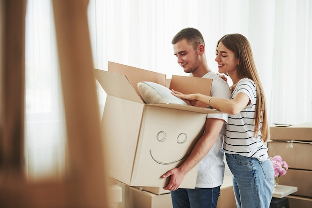 Doos met glimlach erop geschilderd. vrolijk jong stel in hun nieuwe appartement. conceptie van verhuizen.
