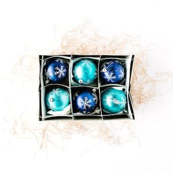 Doos met heldere blauwe kerstballen op witte achtergrond.