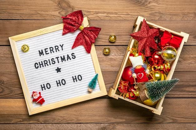 Doos met kerstmisspeelgoed - boog, bal, ster, lint, kerstboom op houten achtergrond