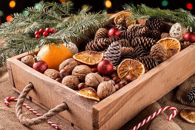 Doos met kerstversiering, noten, kegels en ornamenten