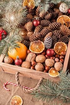 Doos met kerstversiering, noten, kegels