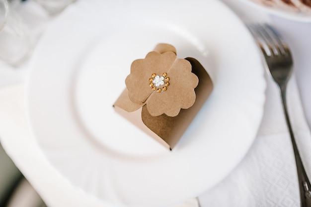 Doos met koekjes op een bord bij gasten. close-up van klein bedankje op plaat bij huwelijksreceptie. luxe cadeau op bord. feest concept. plat leggen. bovenaanzicht.