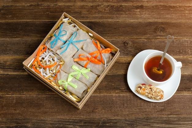 Doos met lekkernijen. een reep muesli en een mok thee. bovenaanzicht