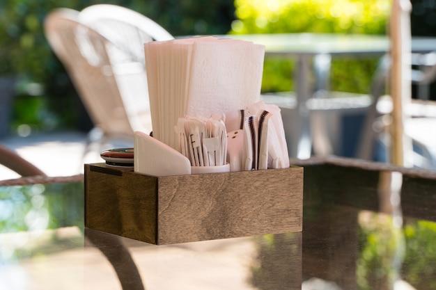 Doos met papieren servetten op een glazen tafel, close-up. onderdeel van de tafelsetting buiten zomercafé