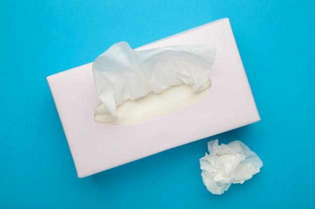 Doos met papieren zakdoekjes op blauwe achtergrond.