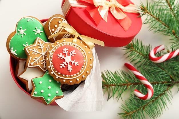 Doos met peperkoekkoekjes, snoepjes en dennenboomtak op witte tafel