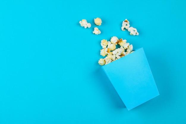 Doos met popcorn gemorst op blauwe achtergrond.